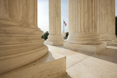 American flag between columns of Supreme Court. An American flag viewed between pillars of Supreme Court building in Washington DC royalty free stock photography