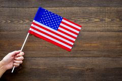 American flag concept. Hand hold small flag on dark wooden background top view copy space. American flag concept. Hand hold small flag on dark wooden background Stock Photos