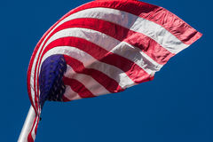 American Flag Curls In Interesting Pattern On Flagpole Stock Photo
