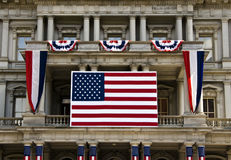 American flag and decoration on a building facade. A large American flag oand various 4th July decorations in front of a building in Washington DC Royalty Free Stock Photography