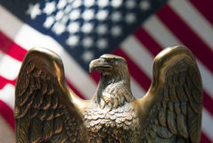 American flag and eagle. A proud bronze eagle statue before an american flag in sunny rays Royalty Free Stock Photos