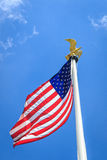 American flag with eagle. American flag waving in the wind, with golden eagle a top of the post Stock Images