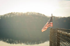 American Flag on Edge of Fence Near Body of Water With Tree Silhouette in the Background Under White Sky Stock Images