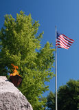 American Flag Eternal Flame. Eternal Flame on rock next to American Flag in Big Springs Park Huntsville Alabama Royalty Free Stock Photo