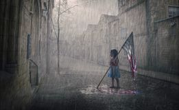 American flag fading away. A little girl holds an American flag that is melting in the rain storm stock photos