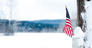 American flag on a fence post before a snowy field. A small American flag juts out from a snow-covered fence post on a cold, snowy day in New Hampshire, USA Stock Photos