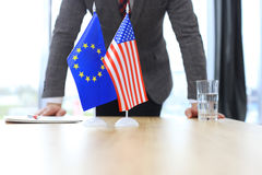 American flag and flag of European Union with businessman near by. Stock Photos