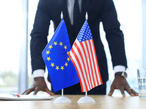 American flag and flag of European Union with businessman near by. Royalty Free Stock Photo