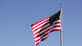 American flag in flag pole waving. American flag blowing in the wind in a clear blue sky background stock footage