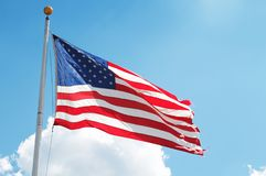 An American Flag on flagpole. An American flag on a flagpole in the blue sky Royalty Free Stock Photography