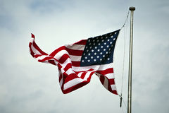 American flag on flagpole. American flag waving in the breeze on top of a flagpole against cloudy skies stock image