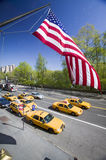 American Flag flies over Central Park in spring with yellow taxies in front of Helmsely Park Lane, Manhattan, New York City, NY Stock Photography
