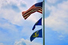 American flag flies in the sun. American flag at the top of the mast flying in the sun royalty free stock photography