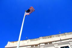 American Flag fluttering in front of building stock image