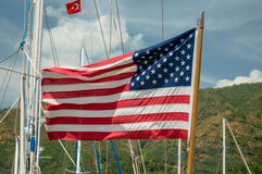 American flag fluttering. The US flag in the wind next to the yachts Royalty Free Stock Photo