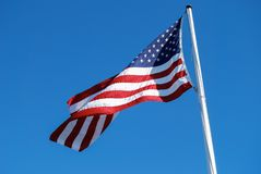 American Flag Wave in Breeze. American flag fluttering in the wind against clear blue sky Stock Image