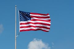 American flag fluttering in the wind. The US flag fluttering in the wind with clouds in the background stock images