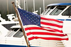 American Flag Flying ALongside Baots in a Harbor Royalty Free Stock Image