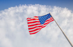 American flag is flying on blue sky. American flag is flying against cloudy blue sky, focus on star of waving flag Stock Photos