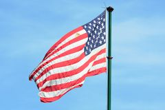 American flag flying in Blue sky Royalty Free Stock Image