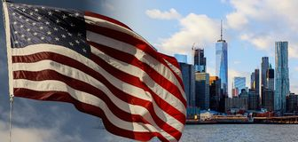 American flag flying the breeze against a blue sky New York, Brooklyn Bridge and Manhattan at the early morning sun light , New Yo Royalty Free Stock Photo