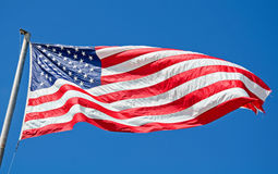 American Flag Flying in Bright Blue Sky Stock Images