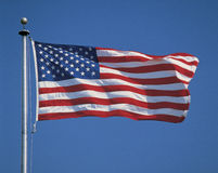 American Flag flying from flagpole. This is an American flag on a flagpole, waving in the wind stock photography