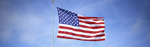 American Flag flying from flagpole. This is a shot of an American flag on a flagpole, waving in the wind against a blue sky royalty free stock photography