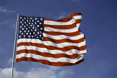 American Flag flying from flagpole. This is an American flag, waving in the wind. It is on a flagpole set against a blue sky with white puffy clouds stock photography