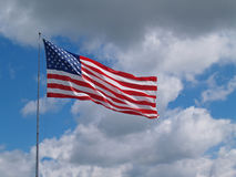 American Flag Flying in front of a Blue Cloudy sky Royalty Free Stock Photography