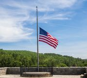 American flag at half staff. American flag flying at half staff against a blue sky with cirrus clouds stock photos