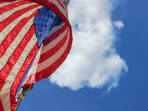 American Flag Flying High. A photo of a flag flying high in the wind with beautiful clouds behind it.  This photo was taken at an angle to give the strength of Stock Image