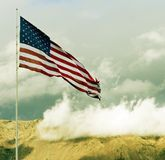 American Flag flying over hilltop with clouds. American flag waving in the wind over mountain range with clouds in the sky stock photos