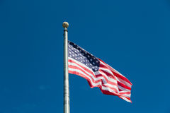 American Flag Flying from Silver Flagpole on Blue Sky Royalty Free Stock Photo