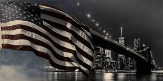 American flag flying the a Skyline view new york city manhattan downtown skyline at night. American flag flying the a Skyline Panoramic view new york city royalty free stock images