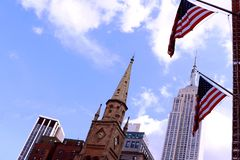 American flag flying in the wind against a blue sky and skyscrapers royalty free stock images