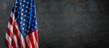 American flag freely hanging against a dark wall Stock Image