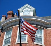 American Flag in Front of Brick Home. The stars and strips blows in the wind in front of a colonial brick home in the embassy district of Washington D.C Stock Photo