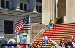 American Flag in front of Federal Hall with people sitting on red stairs on the front, wall street, Manhattan, New York City royalty free stock photos