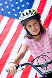 American flag and girl on bike Stock Photo