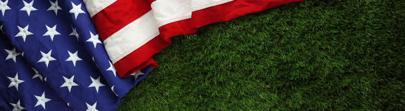 American flag on grass for Memorial Day or Veteran`s day background. Red, white, and blue American flag on grass for Memorial Day or Veteran`s day background Royalty Free Stock Photography