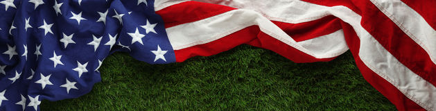American flag on grass for Memorial Day or Veteran`s day background. Red, white, and blue American flag on grass for Memorial Day or Veteran`s day background Royalty Free Stock Images