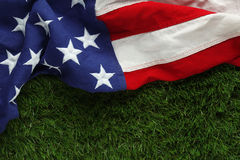 American flag on grass for Memorial Day or Veteran`s day background. Red, white, and blue American flag on grass for Memorial Day or Veteran`s day background Royalty Free Stock Photo