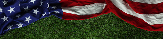 American flag on grass for Memorial Day or Veteran`s day background. Red, white, and blue American flag on grass for Memorial Day or Veteran`s day background Royalty Free Stock Image