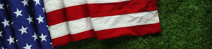 American flag on grass for Memorial Day or Veteran`s day background. Red, white, and blue American flag on grass for Memorial Day or Veteran`s day background Stock Images