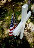 American flag on grave. A closeup of a grave with a clean white crucifix and small American flag stuck into it. This was taken in a military cemetery royalty free stock photo