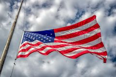 American Flag at Half-Staff. American flag at half-mast or half-staff blowing in wind with blue sky and clouds stock images