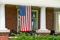 American flag hanging on front porch. Old brick house with white pillars and American flag hanging on porch Royalty Free Stock Images