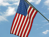 American flag hanging from staff. And framed by blue sky and clouds Royalty Free Stock Images