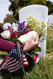 American Flag and Headstones at United States National Cemetery. Headstones, person placing floral arrangement, and Flags at National Military Cemetery stock photos